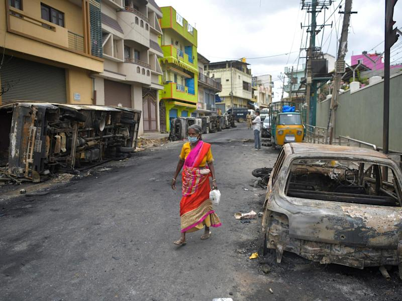 A resident walks past the burned-out remains of a car following protests in the city of Bengaluru, India, over a Facebook post about the Prophet Mohammed: Manjunath Kira/Getty