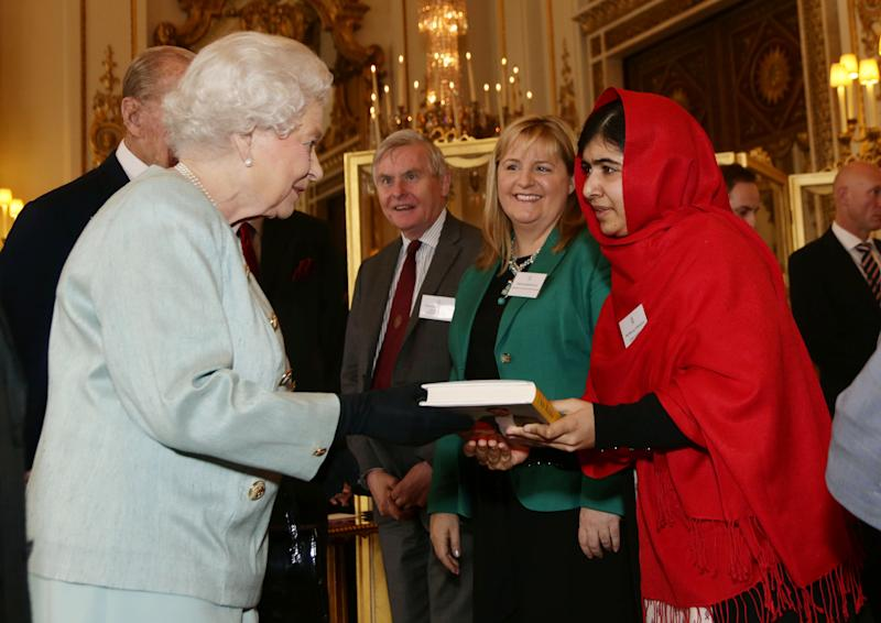 """FILE - In this Oct. 18, 2013, file photo Malala Yousafzai gives a copy of her book """"I Am Malala"""" to Queen Elizabeth II of Great Britain during a reception for youth, education and the Commonwealth at Buckingham Palace, London. The 16-year-old girl from Pakistan, who was shot in the head by the Taliban last October for advocating education for girls, has inspired the development of school curriculum encouraging advocacy. George Washington University announced Monday, Oct. 14, that faculty members are creating curriculum tools to accompany her book, and that several faculty members will pilot the curriculum early next year for both college and high school instruction. (AP Photo/Yui Mok, Pool)"""