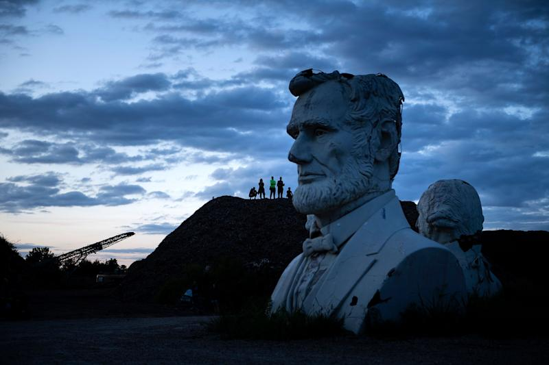 Busts of former US Presidents Abraham Lincoln and George Washington can be seen as people get an overview from a mountain of mulch while they tour the decaying remains of salvaged busts of former US Presidents August 25, 2019, in Williamsburg, Virginia. (Photo: Brendan Smialowski/AFP/Getty Images)