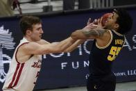 Michigan's Eli Brooks tries to grab a rebound in front of Wisconsin's Tyler Wahl during the second half of an NCAA college basketball game Sunday, Feb. 14, 2021, in Madison, Wis. (AP Photo/Morry Gash)