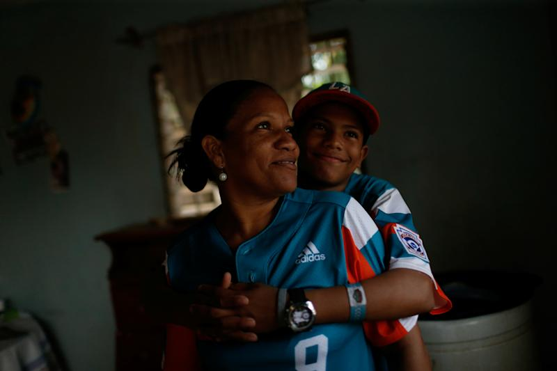 Diana Nunez, 44, mother of baseball little league player Adrian Salcedo, 13, poses for a photograph with her son at their house in Maracaibo, Venezuela. (Photo: Manaure Quintero/Reuters)