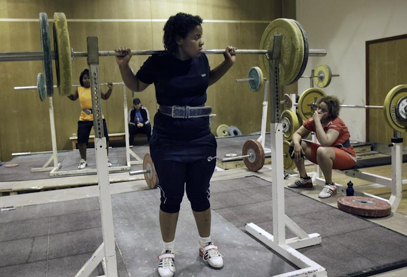 In this Monday, June 18, 2012 photo, Khadija Mohammed, front, who competes in the 75-kilogram category and will be the first female lifter from the Gulf at the Olympics and the first Emirati to qualify for the Olympics outright, practices at the Al Shabab stadium in Dubai, United Arab Emirates. (AP Photo/Kamran Jebreili)