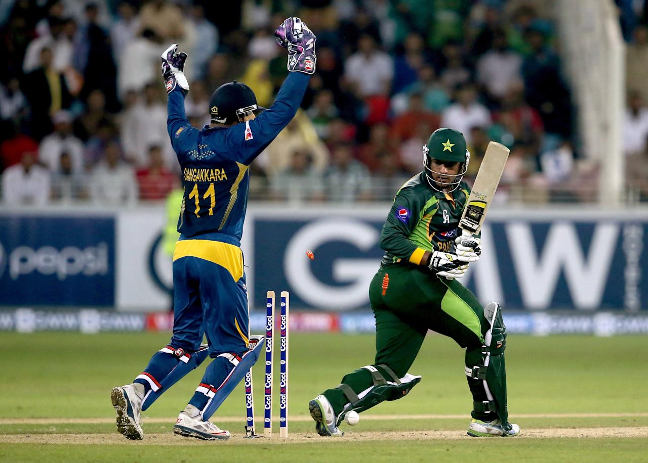 DUBAI, UNITED ARAB EMIRATES - DECEMBER 13:  Sharjeel Khan of Pakistan is dismissed by Seekuge Prasanna of Sri Lanka during the second Twenty20 International match between Pakistan and Sri Lanka at Dubai Sports City Cricket Stadium on December 13, 2013 in Dubai, United Arab Emirates.  (Photo by Francois Nel/Getty Images)