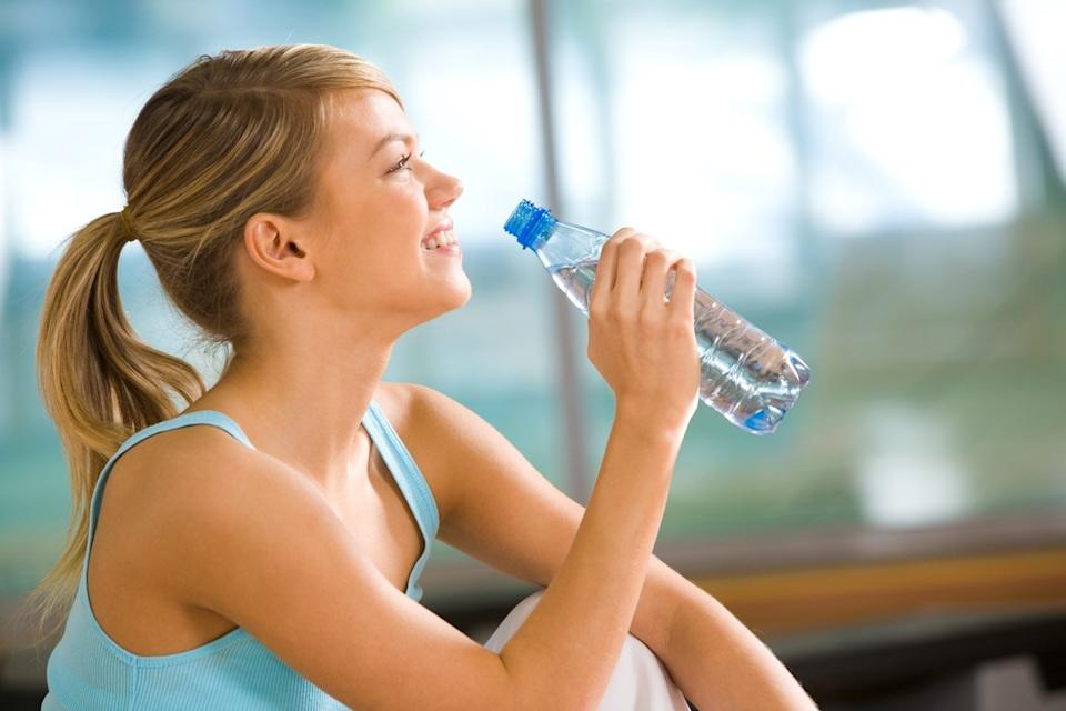 woman going to drink some water from plastic bottle after workout
