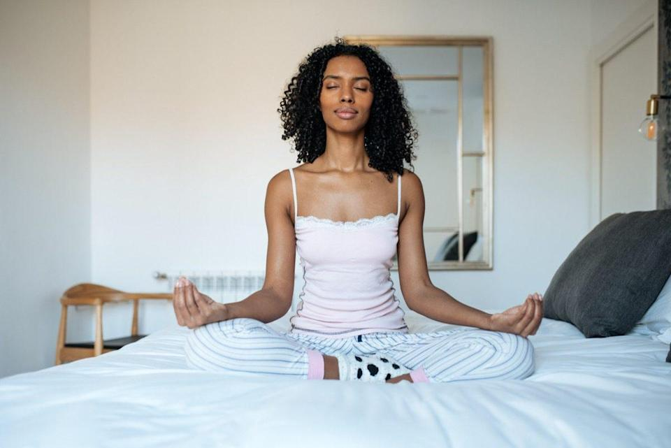 woman sitting in lotus position on bed meditating
