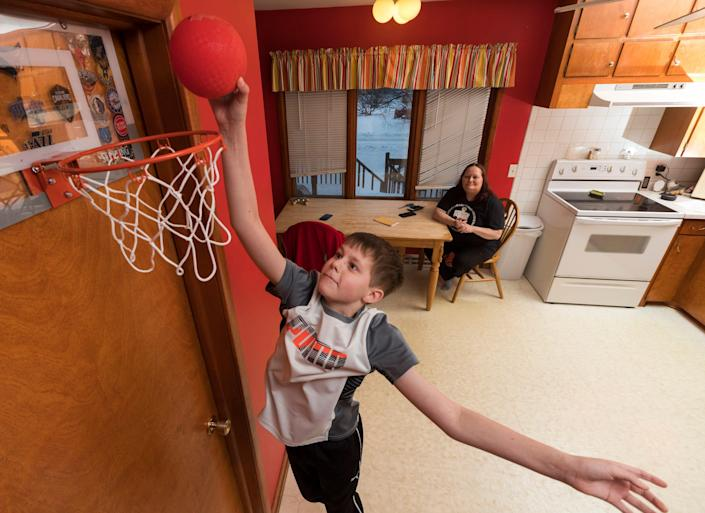 Dawson Bornheimer, 11, plays basketball in the kitchen at his home. When he was an infant, he tested positive for severe combined immunodeficiency and was cured with a transplant of umbilical cord blood, which is similar to a bone marrow transplant.