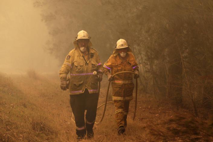 Firefighters drag their water hose after putting out a spot fire near Moruya, Australia, Saturday, Jan. 4, 2020. Australia's Prime Minister Scott Morrison called up about 3,000 reservists as the threat of wildfires escalated Saturday in at least three states with two more deaths, and strong winds and high temperatures were forecast to bring flames to populated areas including the suburbs of Sydney. (AP Photo/Rick Rycroft)