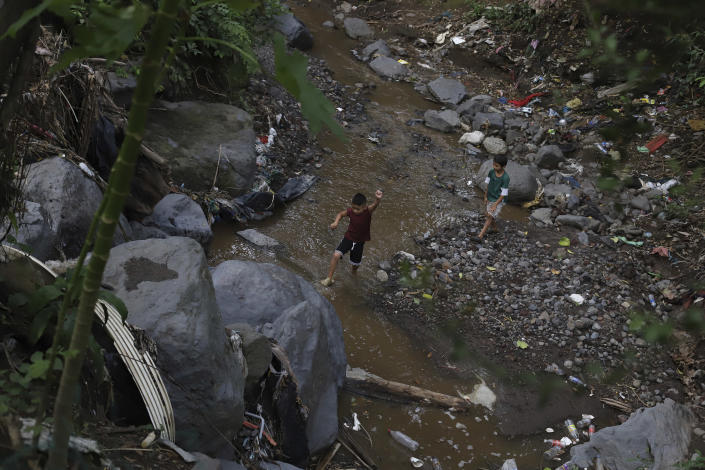 Anderson Zelaya and a friend play in a river littered with debris leftover from last year's October 2020 landslide, in Los Angelitos, El Salvador, Wednesday, July 28, 2021. The 2020 Atlantic hurricane season, one of the worst ever for Central America, wiped out homes and crops and displaced more than half a million people. (AP Photo/Salvador Melendez)