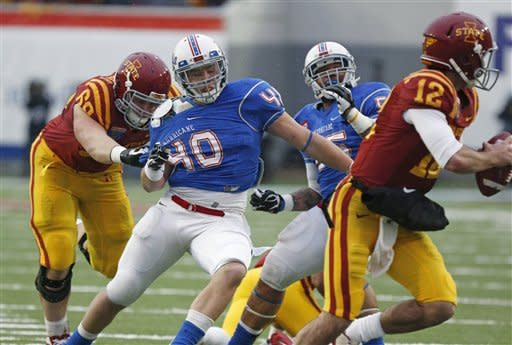 Tulsa linebacker Trent Martin (40) is tied up by Iowa State offensive linesman Kyle Lichtenberg (69) as he pursues Iowa State quarterback Sam B. Richardson (12) in the second quarter of the Liberty Bowl NCAA college football game in Memphis, Tenn., Monday, Dec. 31, 2012. (AP Photo/Rogelio V. Solis)