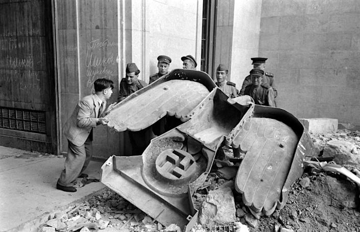 """Unpublished: Russian soldiers and a civilian struggle to move a large bronze Nazi Party eagle which once loomed over a doorway of the Reich Chancellery in Berlin, 1945. (William Vandivert—Time & Life Pictures/Getty Images) <br> <br> <a href=""""http://life.time.com/history/inside-hitlers-bunker-rare-and-unpublished-photos/#1"""" rel=""""nofollow noopener"""" target=""""_blank"""" data-ylk=""""slk:Click here"""" class=""""link rapid-noclick-resp"""">Click here</a> to see the complete collection of pictures and read the full story at LIFE.com"""