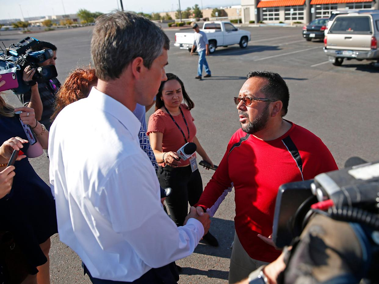 Democratic presidential candidate Beto O'Rourke shakes hands with shooting survivor Carlos Santos near the Walmart shooting scene in El Paso on Aug. 3, 2019. Santos was in the checkout line with his father when gunfire erupted.