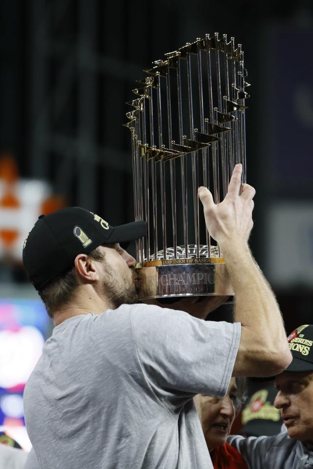 FILE - In this Oct. 30, 2019, file photo, Washington Nationals' Max Scherzer celebrates after Game 7 of the baseball World Series against the Houston Astros in Houston. The last time these teams played the Nationals were celebrating their World Series title in Houston. Since then the Astros have become the league's villains, with a sign-stealing scandal tarnishing their reputation and casting a shadow on their 2017 title. (AP Photo/Matt Slocum, File)