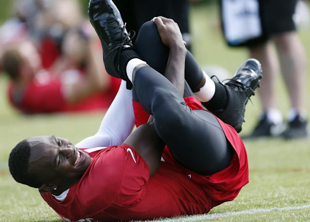 Atlanta Falcons receiver Julio Jones laughs with a teammate as he stretches during an NFL football practice in Flowery Branch, Ga., Tuesday, June 10, 2014. Jones, who missed most of last season with a foot injury, says he hasn't been cleared to practice but stretched during team's workout. (AP Photo/John Bazemore)