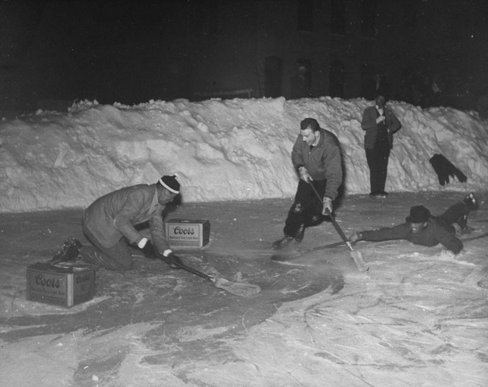 <p>While playing a game of pond hockey, Gary Cooper sneaks by his opponent and charges toward the goal. He was on a ski vacation circa 1949. </p>