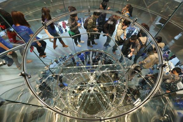 BEIJING, CHINA - OCTOBER 20:  Chinese customers walk along the spiral steps of the newly opened Apple Store in Wangfujing shopping district on October 20, 2012 in Beijing, China. Apple Inc. opened its sixth retail store on the Chinese mainland Saturday. The new Wangfujing store is Apple's largest retail store in Asia.  (Photo by Feng Li/Getty Images)