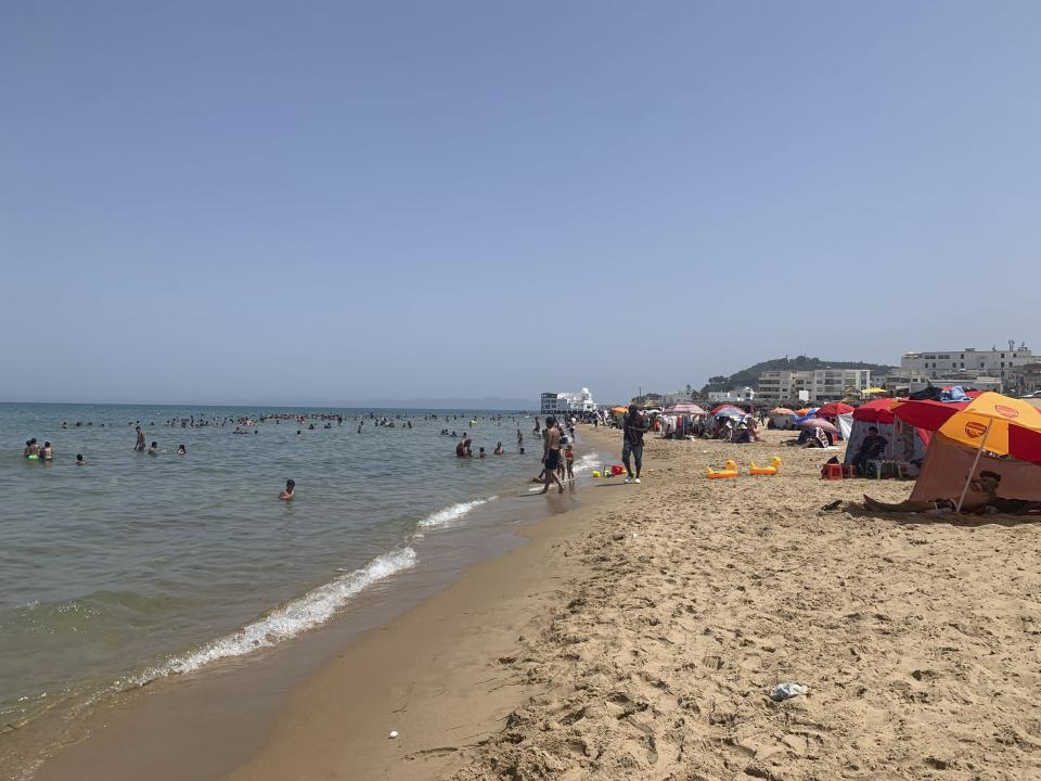 Tunisians relax on La Marsa beach outside Tunis, Sunday, Aug. 1, 2021, as the country remained in limbo more than a week after President Kais Saied fired the prime minister, froze the parliament and took on executive powers. (AP Photo/Francesca Ebel)