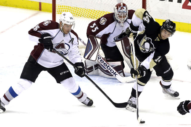 Pittsburgh Penguins' Chris Kunitz (14) works to control the puck against Colorado Avalanche's Paul Stastny (26) in front of Colorado Avalanche goalie Jean-Sebastien Giguere (35) during a first-period power play in an NHL hockey game in Pittsburgh Monday, Oct. 21, 2013. (AP Photo/Gene J. Puskar)