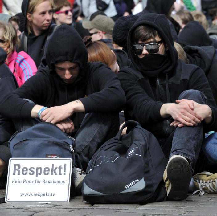 """Participants of a sit-in block a street to protest against an election campaign of the German right-wing party NDP in Neumuenster, northern Germany, Tuesday, May 1, 2012. Board reads """"Respect! No space for racism"""". (AP Photo/dapd, Tim Riediger)"""