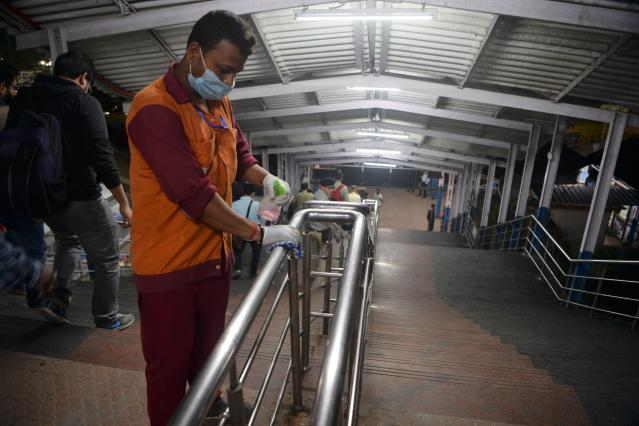 A worker wearing a facemask amid concerns over the spread of the COVID-19 disinfects the hand rail of a staircase at New Jalpaiguri railway station on the outskirts of Siliguri.