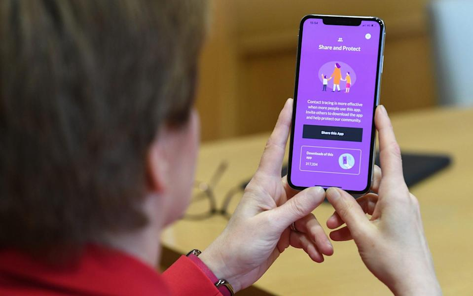 Nicola Sturgeon examines Scotland's Covid app during its launch in September - Jeff J Mitchell/Getty Images Europe