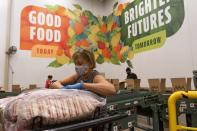 Volunteers pack boxes of food for distribution, at The Capital Area Food Bank, Tuesday, Oct. 5, 2021, in Washington. (AP Photo/Jacquelyn Martin)