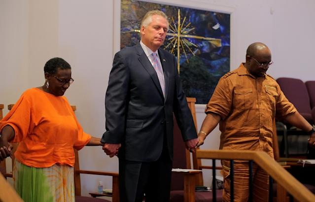 """<p>Virginia Governor Terry McAuliffe (C) holds hands with Deaconess Beverly Terrell (L) and Pastor Alvin Edwards as members of Charlottesville's Mt. Zion First African Baptist Church pray during Sunday services the morning after the attack on counter-protesters at the """"Unite the Right"""" rally organized by white nationalists in Charlottesville, Virginia, U.S., August 13, 2017. (Jim Bourg/Reuters) </p>"""