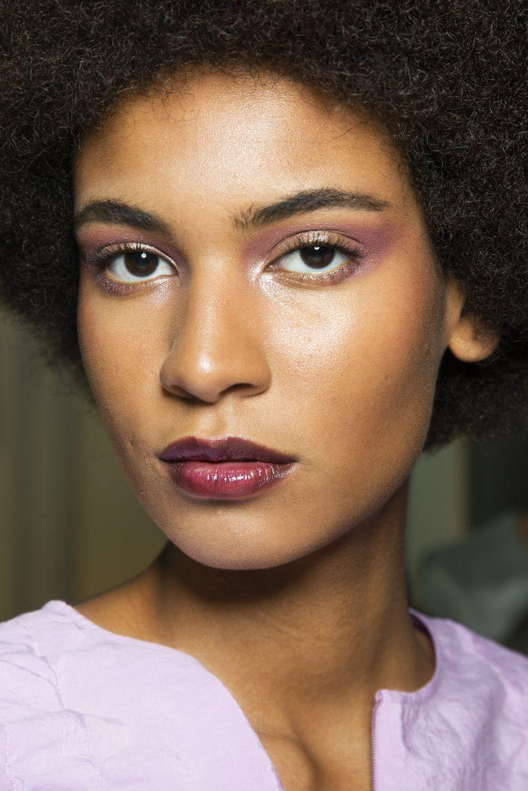 <p>A glossy plum lip with a lilac eye is our favorite color combo of the season.</p>