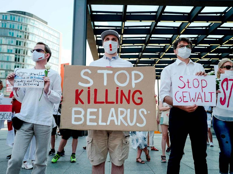 """A protester holds a sign reading """"Stop Killing Belarus"""" during a demonstration on the contested elections in Belarus: AFP via Getty Images"""
