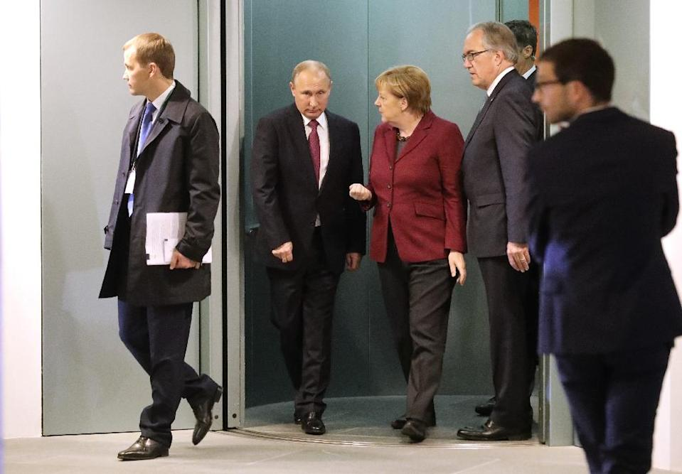 German Chancellor Angela Merkel (3L) talks to Russian President Vladimir Putin at the chancellery in Berlin (AFP Photo/Michael Kappeler)