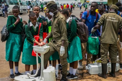 Secondary school students wash their hands before returning home in Rwanda