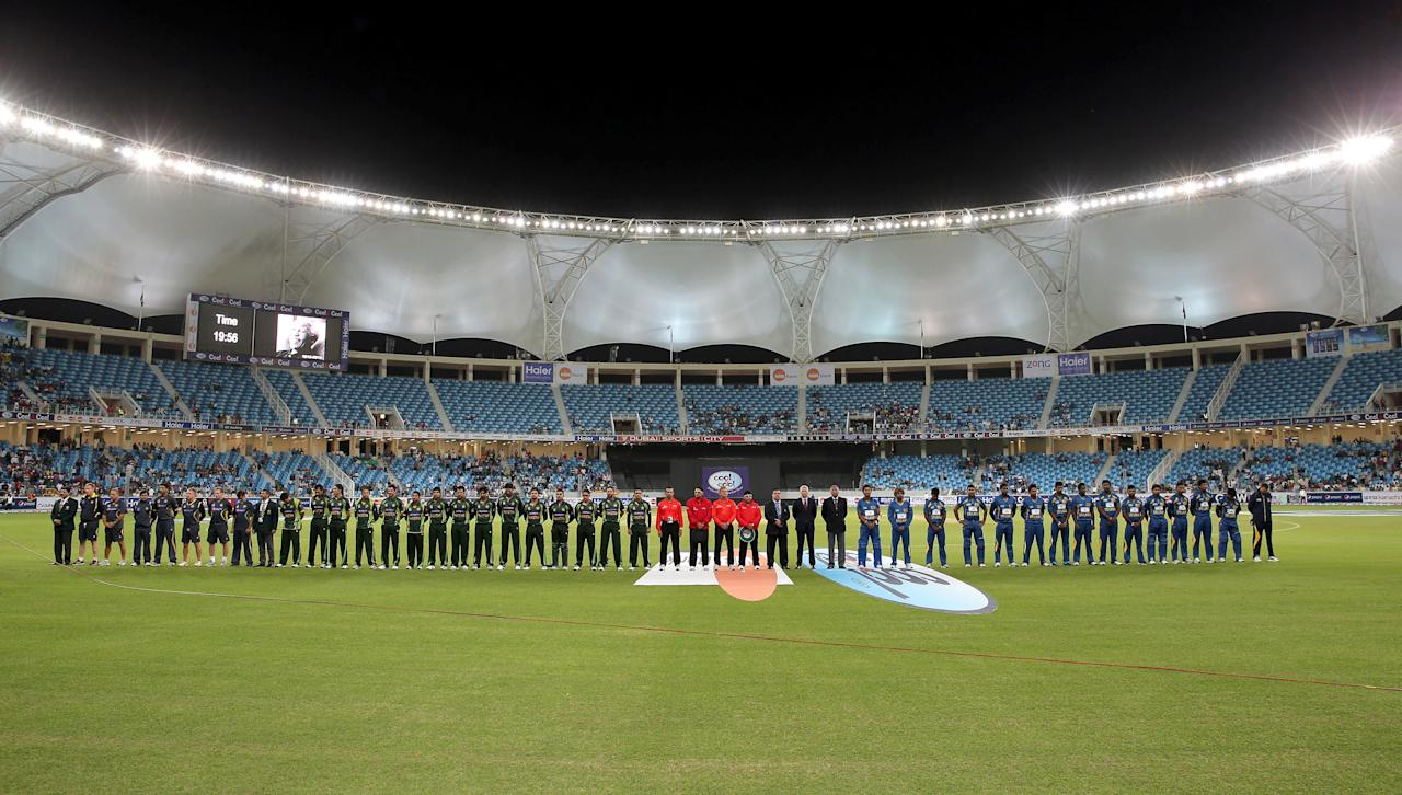 DUBAI, UNITED ARAB EMIRATES - DECEMBER 11:  The teams of Pakistan and Sri Lanka line up during a minute of silence for Nelson Mandela prior to the first Twenty20 International match between Pakistan and Sri Lanka at Dubai Sports City Cricket Stadium on December 11, 2013 in Dubai, United Arab Emirates.  (Photo by Francois Nel/Getty Images)