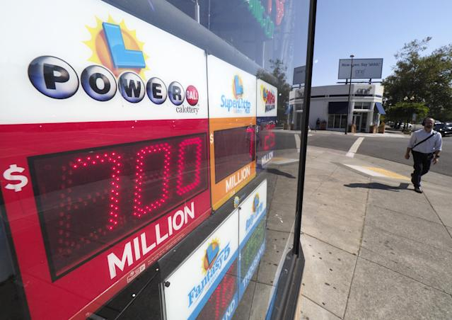 <p>A pedestrian walks by a liquor store displaying a Powerball sign in Oakland, Calif., on Aug. 23, 2017. The Powerball lottery has risen to 700 million US dollars making it one of the largest in history. (Photo: John G. Mabanglo/EPA/REX/Shutterstock) </p>