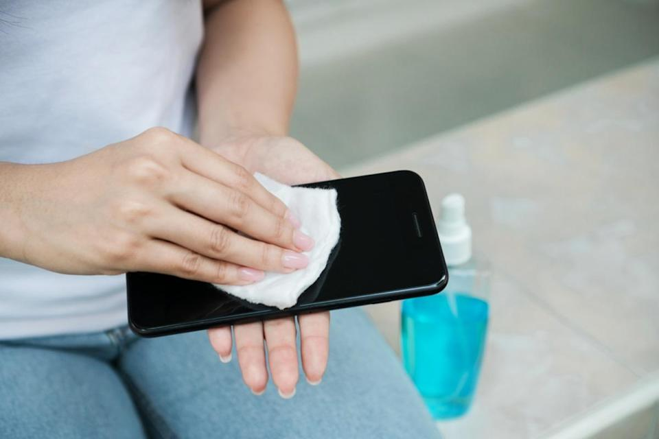 Woman cleaning smartphone screen with alcohol
