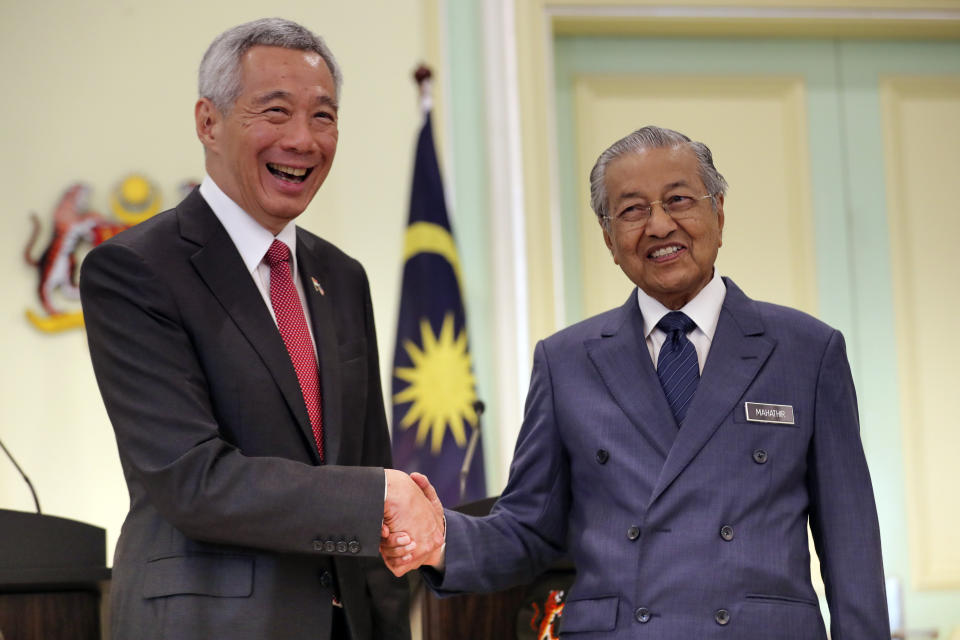 Malaysian Prime Minister Mahathir Mohamad, right, shakes hands with Singaporean Prime Minister Lee Hsien Loong after a press conference in Putrajaya, Malaysia, Tuesday, April 9, 2019. Lee is in Malaysia for a two-day working visit. (AP Photo/Vincent Thian)