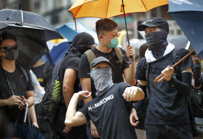 A protester prepares to throw an egg at a pro-government lawmaker during a march in Hong Kong Saturday, Aug. 17, 2019. Another weekend of protests got underway in the Chinese territory as Mainland Chinese police are holding drills in nearby Shenzhen, prompting speculation they could be sent in to suppress the protests. (AP Photo/Vincent Thian)