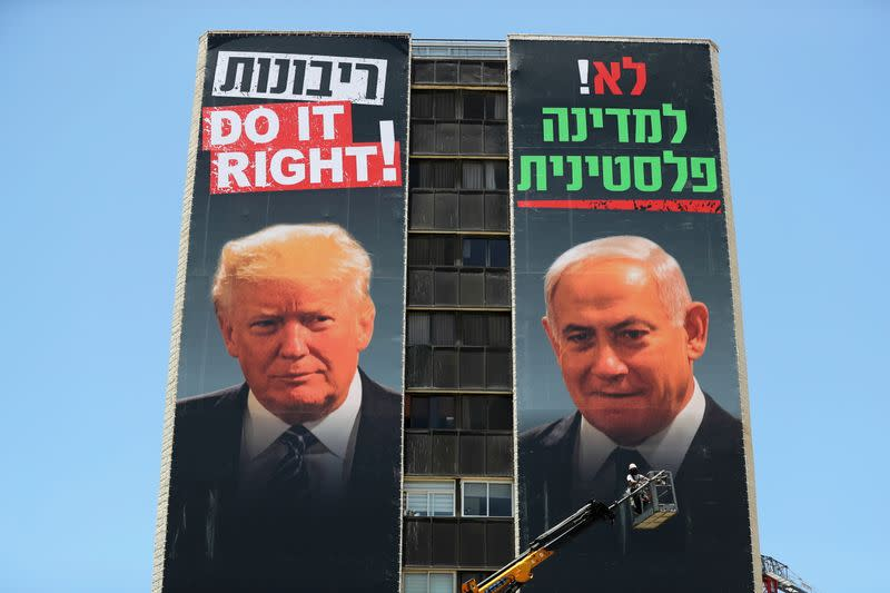 FILE PHOTO: A labourer puts up banners depicting U.S. President Donald Trump and Israeli Prime Minister Benjamin Netanyahu, part of a new campaign by the umbrella Yesha Jewish settler council in Jerusalem