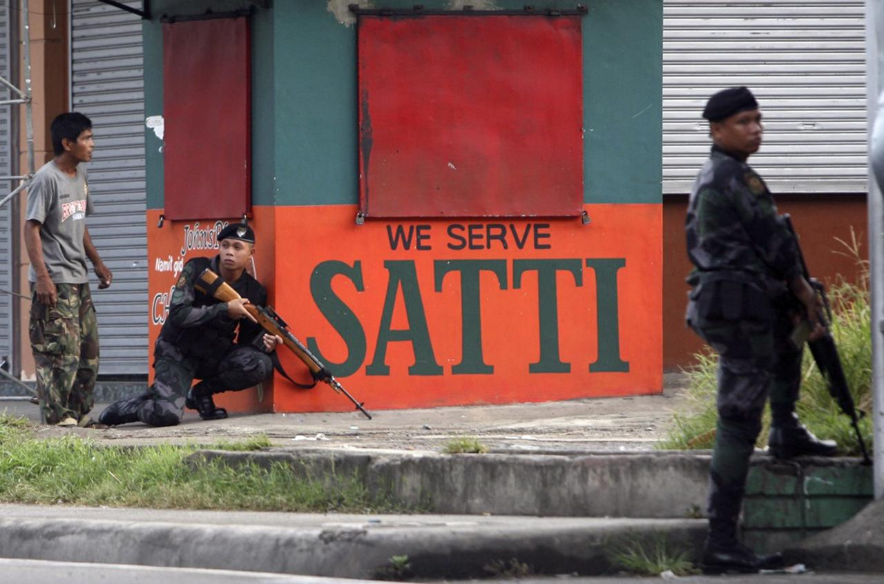 A combat police sniper (L) takes position during an encounter with rebels from the Moro National Liberation Front (MNLF) in downtown Zamboanga City