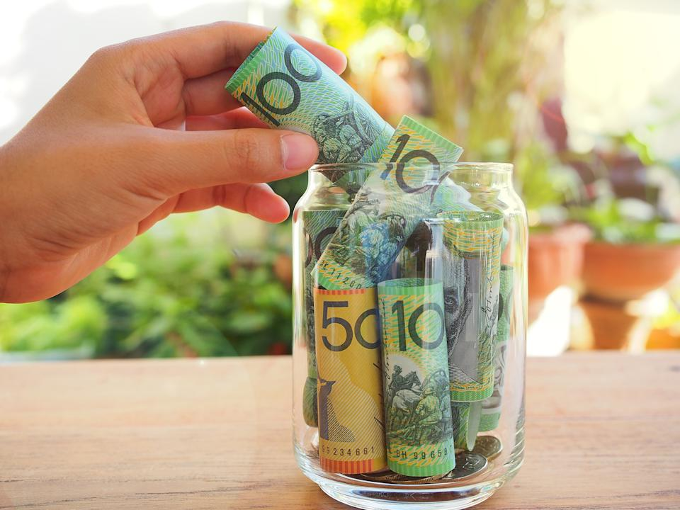 Close-Up Of Hand Inserting Paper Currency In Bottle