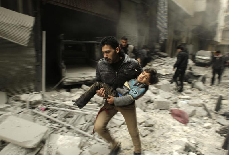 A man runs as he carries a child who survived from what activists say was an airstrike by forces loyal to Syrian President Bashar al-Assad, at al-Ferdaws in Aleppo