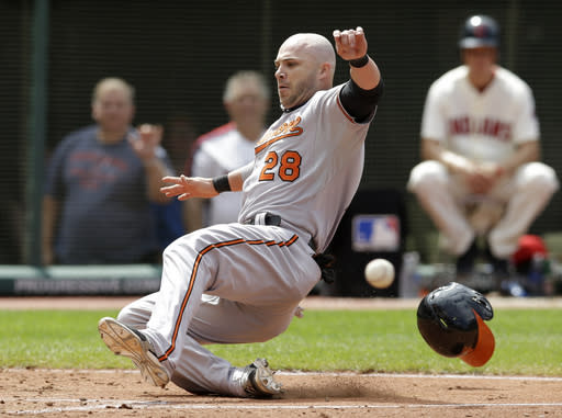 Baltimore Orioles' Steve Pearce scores ahead of the ball on a single by J.J. Hardy in the sixth inning of a baseball game against the Cleveland Indians, Sunday, Aug. 17, 2014, in Cleveland. (AP Photo/Tony Dejak)
