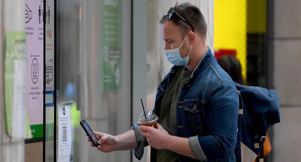 A person uses a smart phone to check-in with a QR code at a supermarket in Pitt Street mall, in Sydney, Saturday, July 17, 2021. Source: AAP