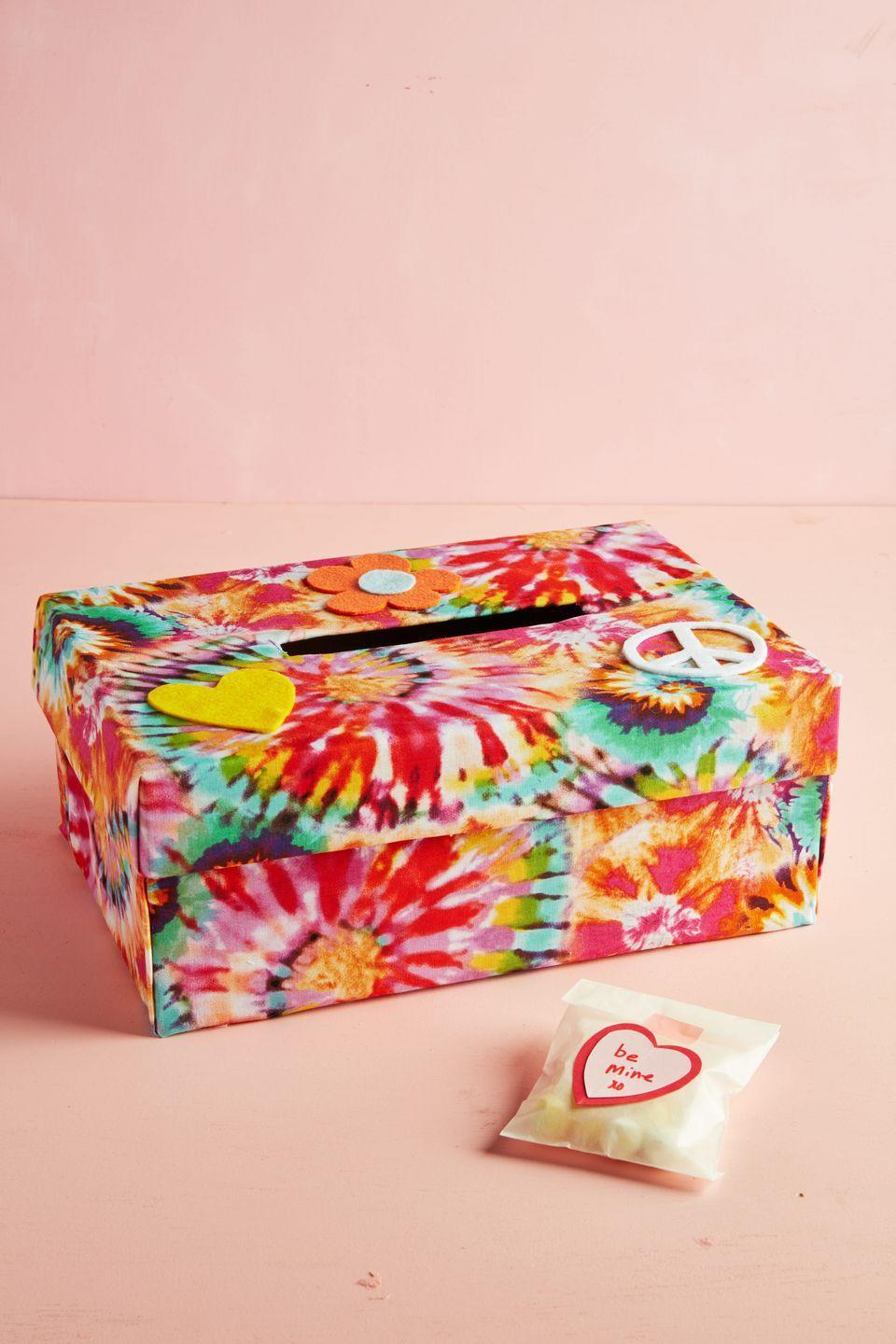 "<p>Spread peace and love with this tie-dye fabric-wrapped box.</p><p><strong>To make:</strong> Cut a slit in the top of a box (you can use a two part box or a folding lid box). Wrap box with tie dye fabric; adhering it with double sided tape or spray adhesive. Cut out decals from felt and glue to the top of the box. <br></p><p><a class=""link rapid-noclick-resp"" href=""https://go.redirectingat.com?id=74968X1596630&url=https%3A%2F%2Fwww.etsy.com%2Fmarket%2Ftie_dye_fabric&sref=https%3A%2F%2Fwww.countryliving.com%2Fdiy-crafts%2Fg25844424%2Fvalentines-day-boxes%2F"" rel=""nofollow noopener"" target=""_blank"" data-ylk=""slk:SHOP TIE DYE FABRIC"">SHOP TIE DYE FABRIC</a></p>"