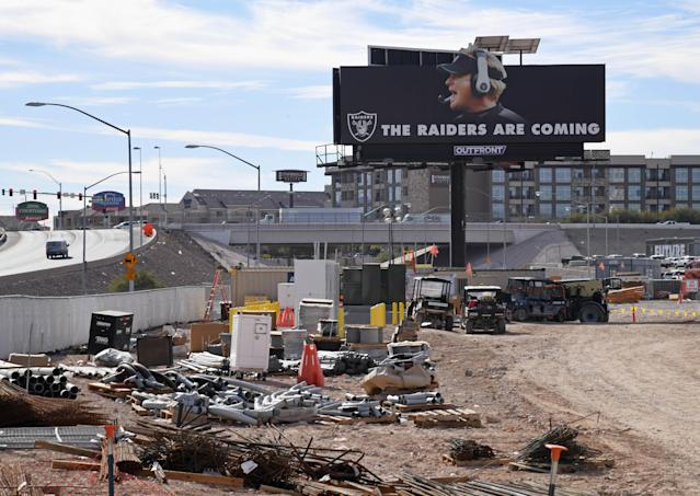 """A billboard featuring the words """"THE RAIDERS ARE COMING"""" and an image of Oakland Raiders head coach Jon Gruden is seen on the construction site of the Raiders' new stadium. (Getty Images)"""