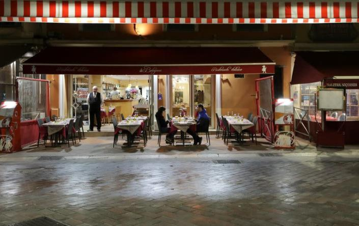 A couple sits in a restaurant, as France's Prime Minister announced to close most all non-indispensable locations, notably cafes, restaurants, cinemas, nightclubs and shops from midnight in Nice