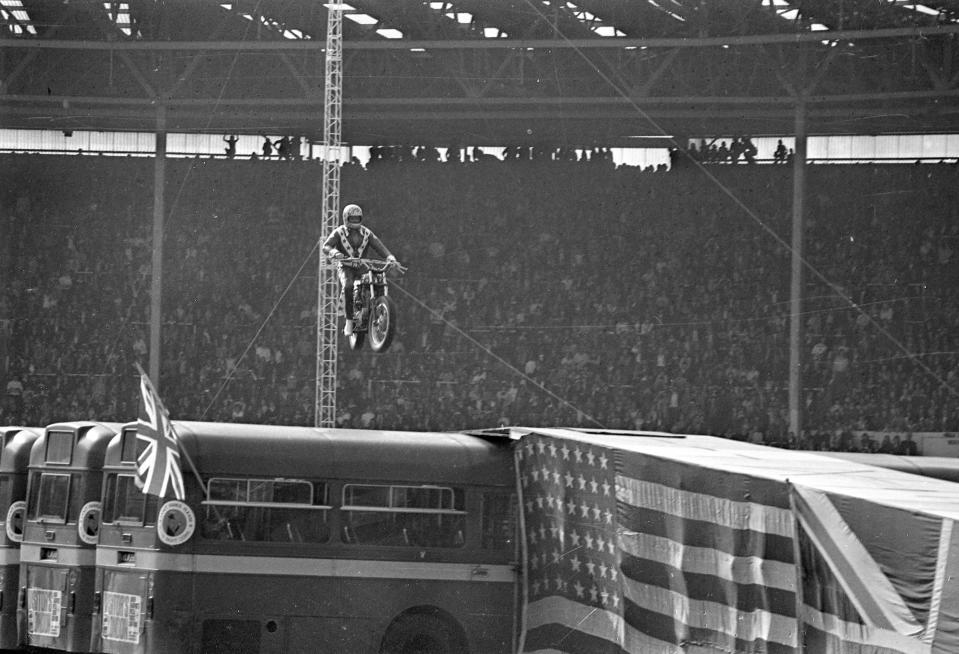 """FILE - In this May 25, 1975, file photo, Evel Knievel approaches the landing ramp with his motorcycle during his unsuccessful effort to leap over 13 busses spanning 140-feet at 100 miles per hour in London. Evel Knievel's son is on a collision course with the Walt Disney Co. and Pixar over a movie daredevil character named Duke Caboom. A federal trademark infringement lawsuit filed Tuesday, Sept. 22, 2020, in Las Vegas accuses the moviemaker of improperly basing the """"Toy Story 4"""" character on Knievel, who died in 2007. (AP Photo, File)"""
