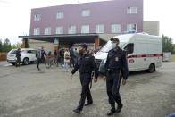 FILE - In this Friday, Aug. 21, 2020 file photo, police patrol an area, as journalists gather at the Omsk Ambulance Hospital No. 1, intensive care unit where Alexei Navalny was hospitalized in Omsk, Russia. Novichok, a deadly nerve agent that has left Russian opposition politician Alexei Navalny in a coma and nearly killed a former Russian spy and his daughter in 2018, was the product of a highly secretive Soviet chemical weapons program. Just a few milligrams of the odorless liquid — the weight of a snowflake — are enough to kill a person within minutes. (AP Photo/Evgeniy Sofiychuk, File)
