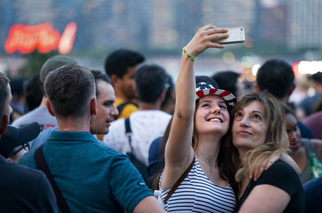 <p>Visitors who said they are from Switzerland take a photo of one another as they wait with other spectators on the east side of Manhattan borough before a fireworks display, part of Independence Day festivities Wednesday, July 4, 2018, in New York. (Photo: Craig Ruttle/AP) </p>