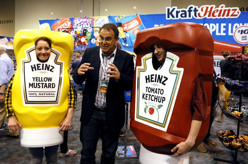 FILE PHOTO: Characters at the Berkshire Hathaway company Kraft Heinz booth pose with a reporter at the shareholder shopping day in Omaha