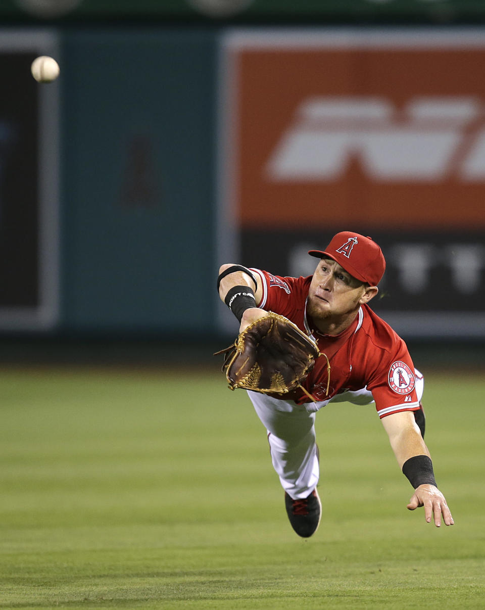 Los Angeles Angels' Kole Calhoun dives to catch a ball hit by Texas Rangers' Ian Kinsler during the fourth inning of a baseball game Wednesday, Aug. 7, 2013, in Anaheim, Calif. (AP Photo/Jae C. Hong)