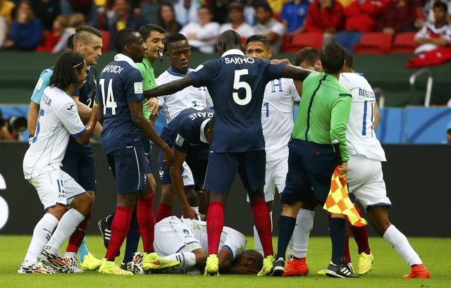 Wilson Palacios of Honduras lies on the pitch during a scuffle with the French players during their 2014 World Cup Group E soccer match at the Beira Rio stadium in Porto Alegre June 15, 2014. Palacios fouled France's Paul Pogba but was kicked at by Pogba in retaliation. Both players were awarded a yellow card for the incident. REUTERS/Damir Sagolj (BRAZIL - Tags: SOCCER SPORT WORLD CUP)